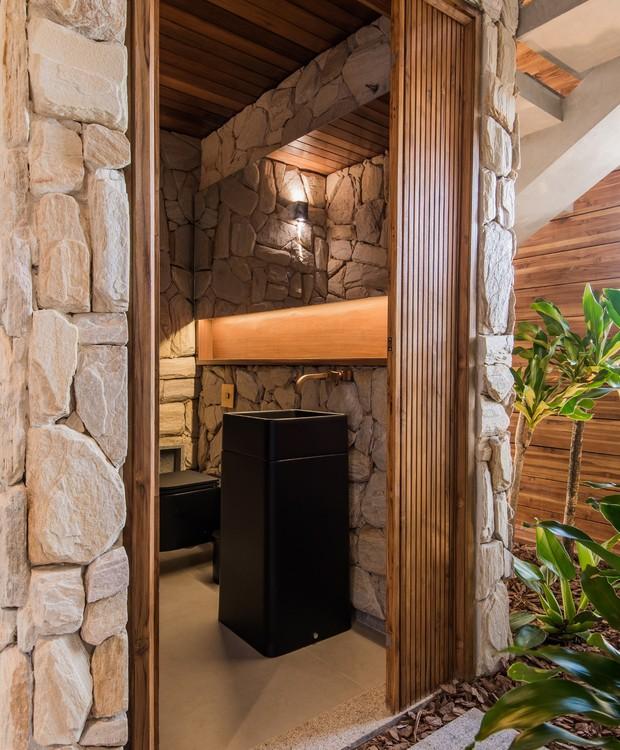 Nesta casa de praia, as paredes foram revestidas com pedra moledo bruta. A cuba de louça preta ganhou companhia de um nicho de madeira iluminado sob o espelho (Foto: Tarso Figueira/Divulgação)