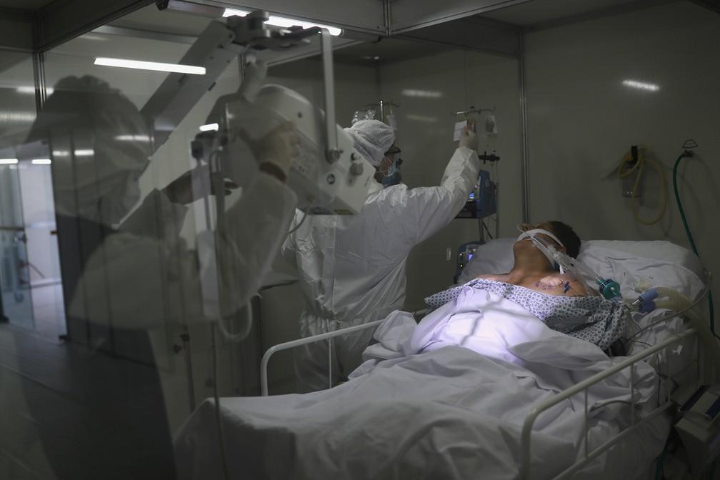 12 de maio - Membros da equipe médica com trajes de proteção e máscaras faciais fazem raio-X do pulmão de paciente na Unidade de Terapia Intensiva (UTI), em um hospital de campanha criado para tratar pacientes com coronavírus (COVID-19), em Guarulhos — Foto: Amanda Perobelli/Reuters