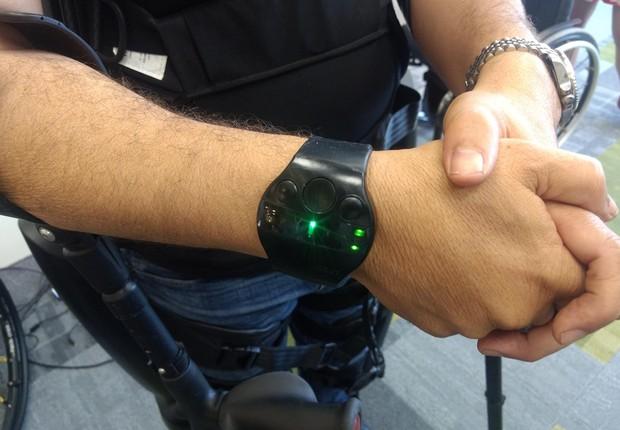 Comando do exoesqueleto é feito parte por movimentos do tronco do usuário, parte pelo controle remoto em forma de relógio (Foto: Época NEGÓCIOS)