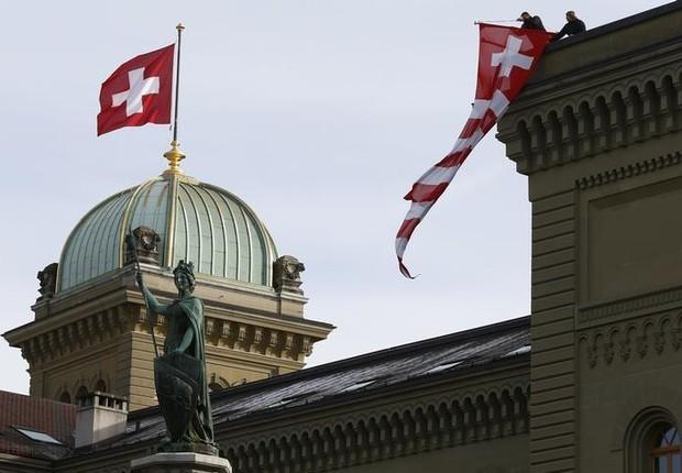 Bandeira da Suíça é vista na sede do Parlamento em Berna (Foto: Ruben Sprich/Reuters)