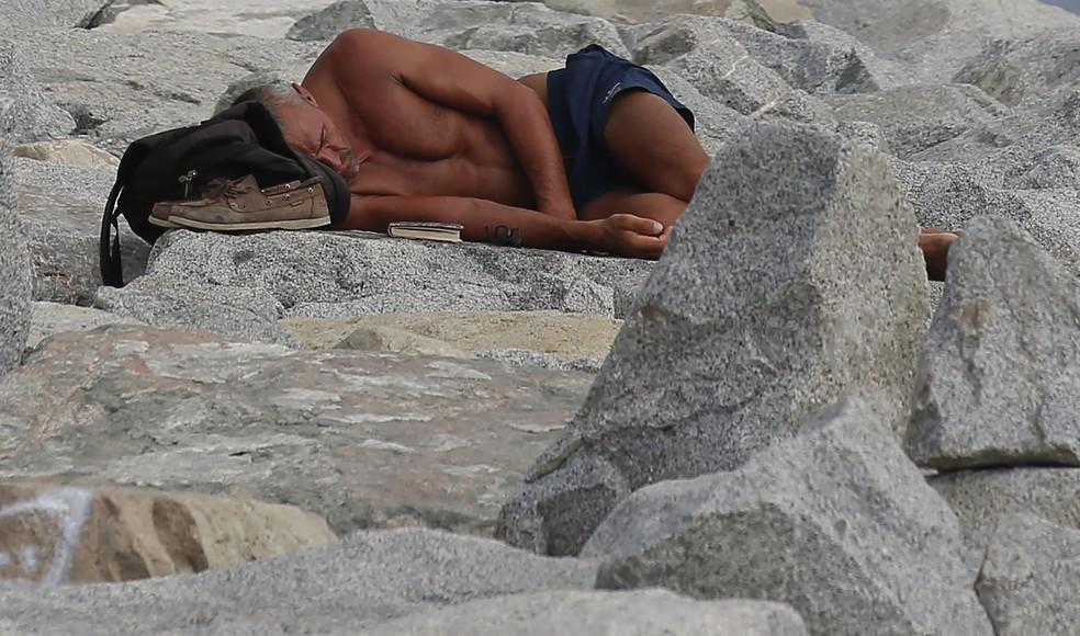 Homem dorme perto de praia em dia de verão em Barcelona, na Espanha (Foto: AP Photo/Manu Fernandez)