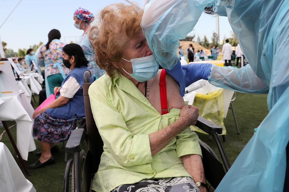 Idosa recebe a primeira dose de vacina contra a Covid-19 em Santiago do Chile, em foto de 3 de fevereiro de 2021 — Foto: Ivan Alvarado/Reuters/Arquivo