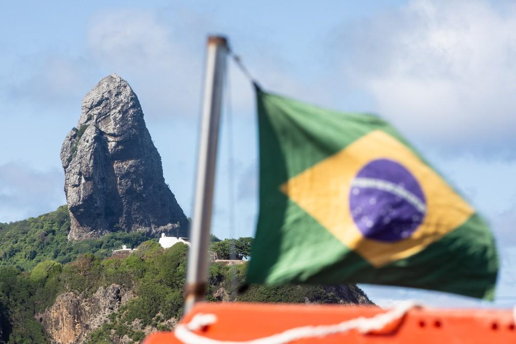 Vento sacode uma bandeira do Brasil num barco de passeio na Praia do Porto, em Noronha, com vista para o Morro do Pico ao fundo — Foto: Fábio Tito/G1