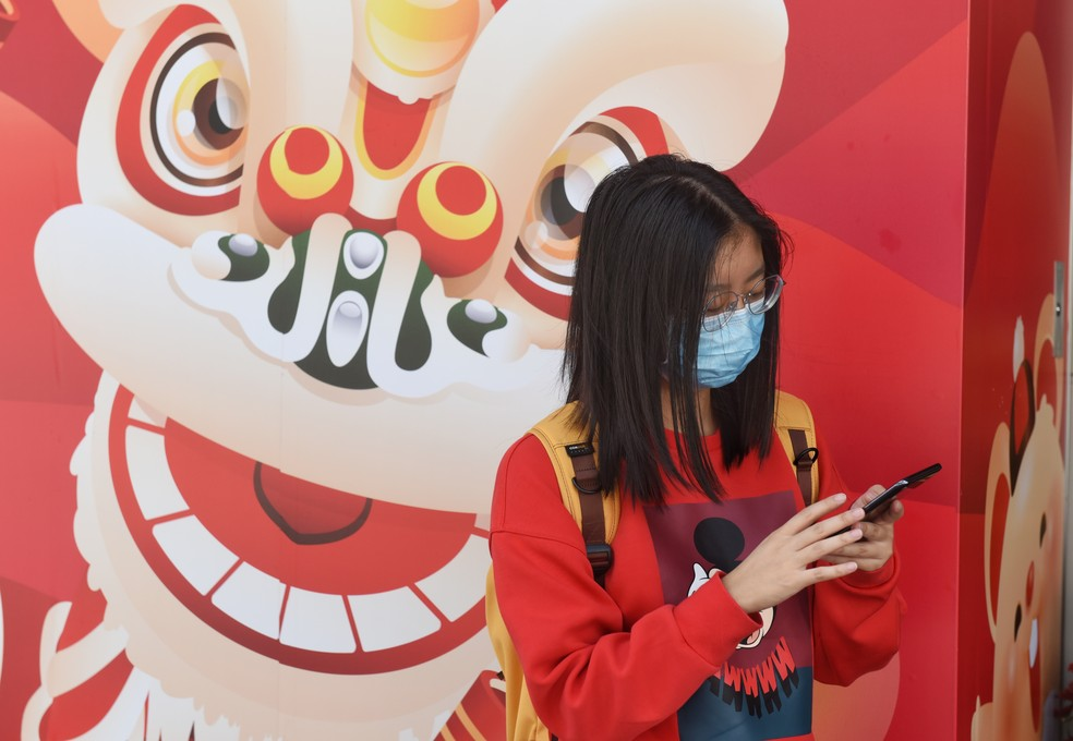Pedestre cobre o rosto com máscara sanitárias após a confirmação dos primeiros casos de coronavírus em Hong Kong, China. Foto de 23 de janeiro de 2018. — Foto: Miguel Candela Poblacion/Anadolu Agency