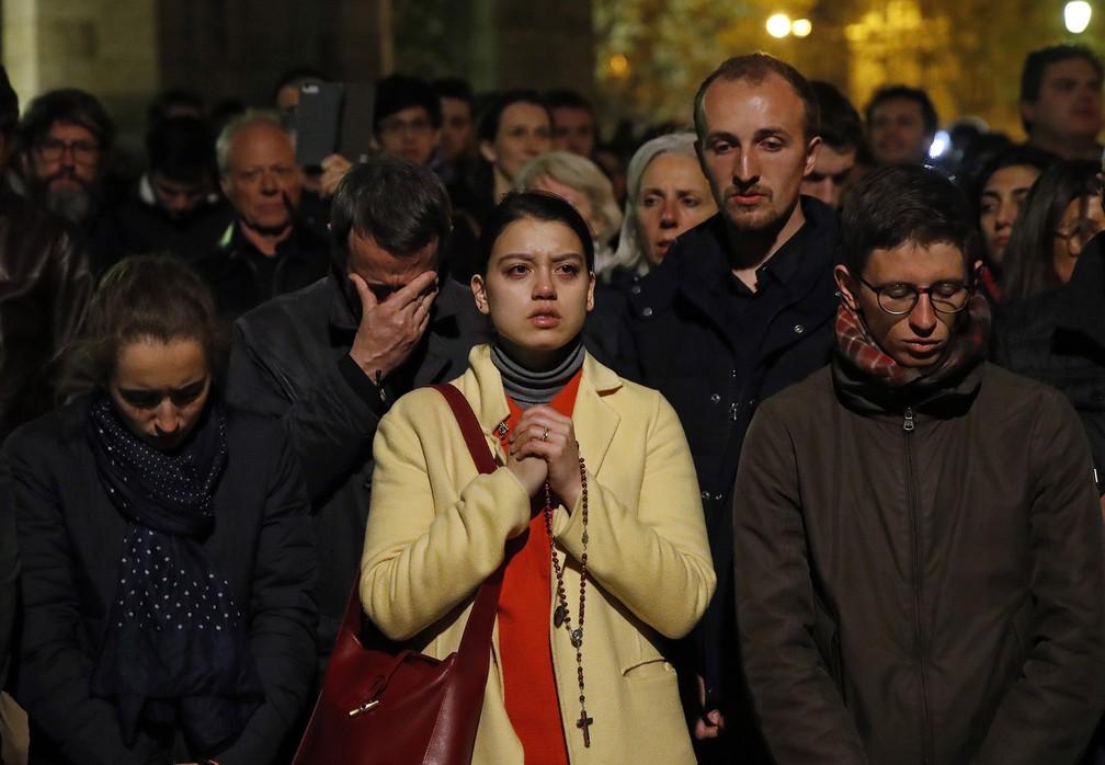 Fiéis rezam enquanto acompanham de longe o combate ao incêndio na Catedral de Notre-Dame, em Paris — Foto: Christophe Ena/AP