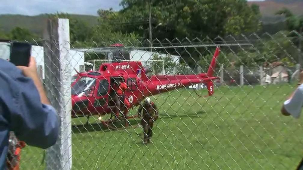 Bombeiros sujos de lama descem de helicóptero que faz busca por vítimas de tragédia com barragem da Vale em Brumadinho (MG) — Foto: Reprodução/TV Globo