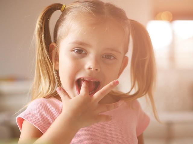 Menina loira de chiquinhas lambendo os dedos (Foto:  thinkstock)