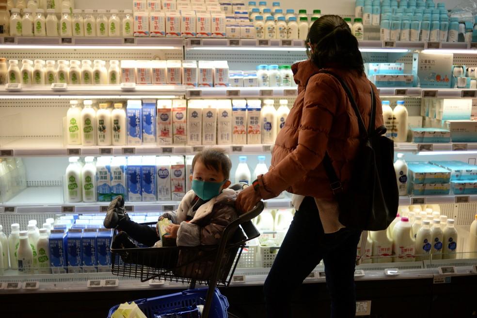Mulher faz compras com bebê usando máscara em Pequim, em meio à epidemia de coronavirus na China — Foto: REUTERS/Tingshu Wang