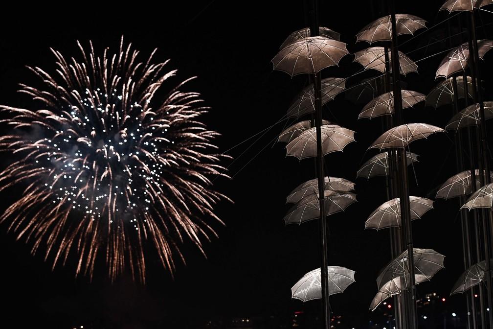 """Fogos de Ano Novo são vistos no golfo de Thermaikos ao lado da escultura """"Guarda-chuvas"""", em Thessaloniki, na Grécia, na teça (31). — Foto: Sakis Mitrolidis / AFP"""