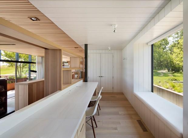 A cozinha branca dá contraste ao resto da casa de madeira (Foto: Michael Moran/ Reprodução)