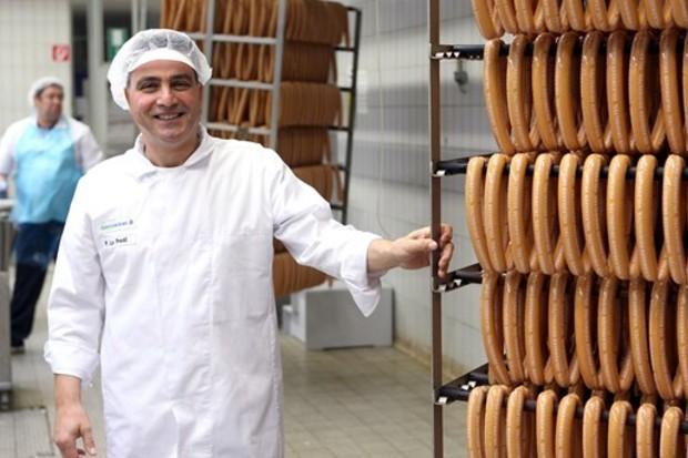Trabalhador posa ao lado de salsichas produzidas na fábrica da Volkswagen (Foto: Divulgação)