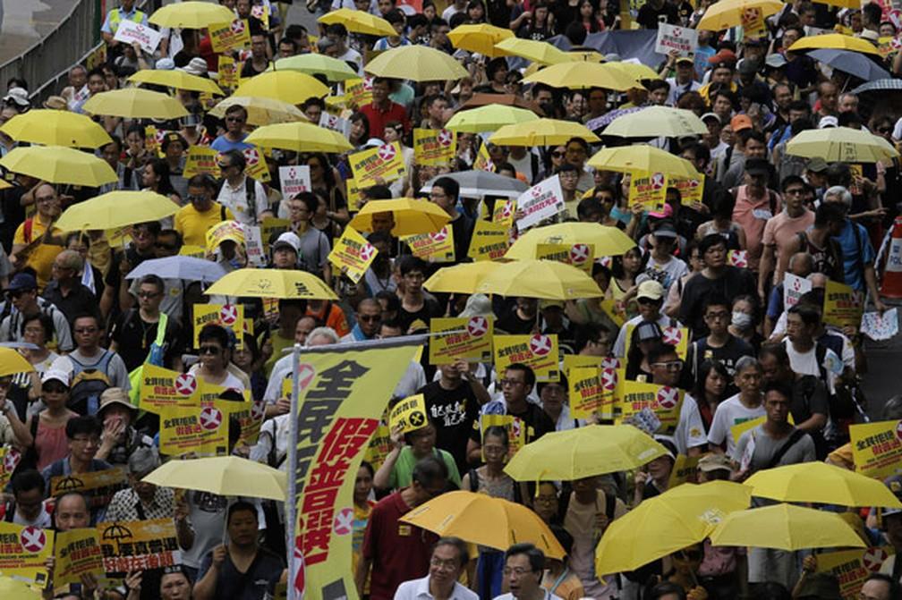 Manifestante carregando guarda-chuvas amarelos participam de protesto pró-democracia em Hong Kong em imagem de 2015 — Foto: Vincent Yu/AP