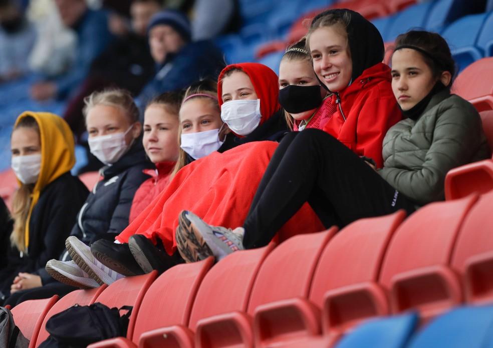 Jovens com máscaras assistem à partida de futebol da Liga Principal Feminina de futebol em Minsk, em Belarus, na quinta-feira (30)  — Foto: Sergei Grits/AP