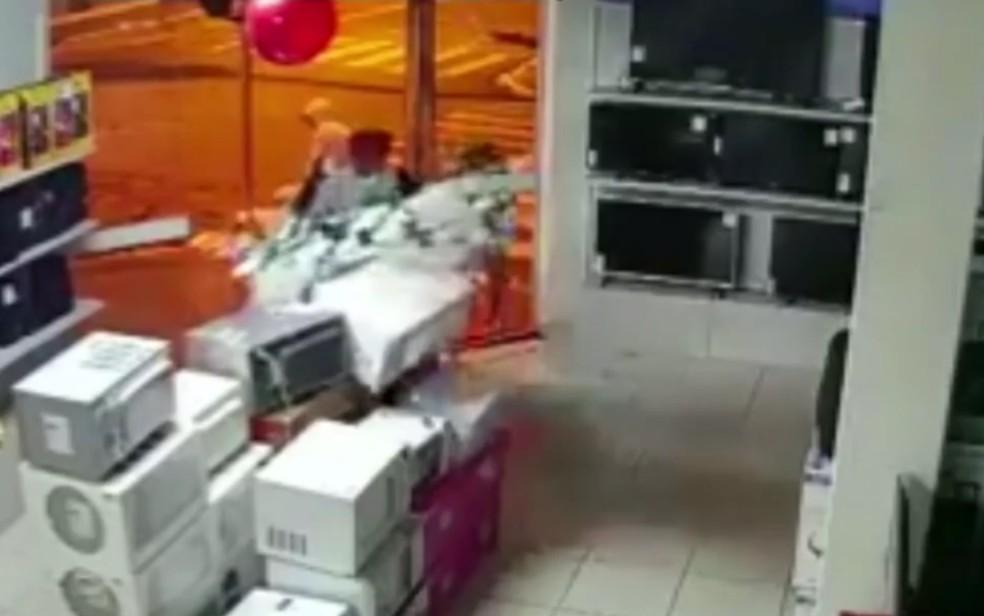 Criminosos quebram porta de vidro para furtar loja, em Caldas Novas — Foto: Reprodução/TV Anhanguera