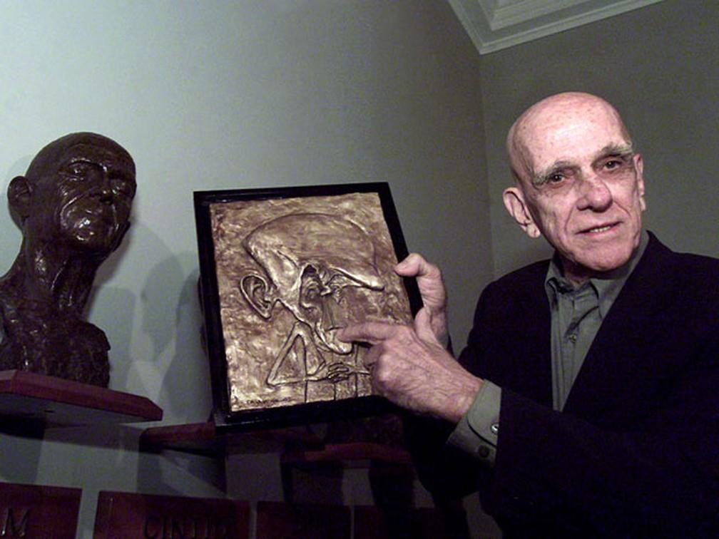 Em foto de 2003, o escritor brasileiro Rubem Fonseca mostra retrato e escultura de bronze, confeccionado pelo artista mexicano Alfredo Lopez Casanova, dedicado a ele durante o Prêmio Guadalajara International Book Fair, no México — Foto: AE/Guillermo Arias/AP