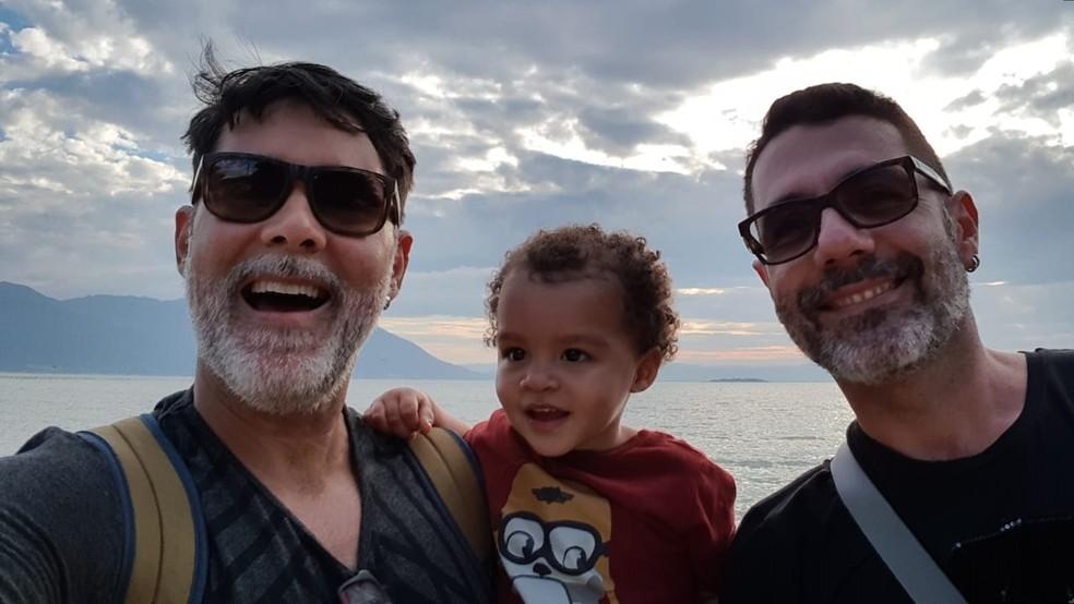 -  Gabriel e seus dois pais, João Carlos Fonseca Martins e George Antônio do Nascimento Souza  Foto: Arquivo pessoal