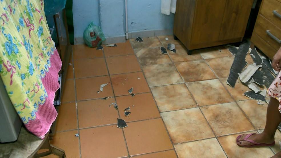Vizinha mostra chão da casa onde pai e bebê caíram em Cariacica, no Espírito Santo — Foto: Luciney Araújo/ TV Gazeta