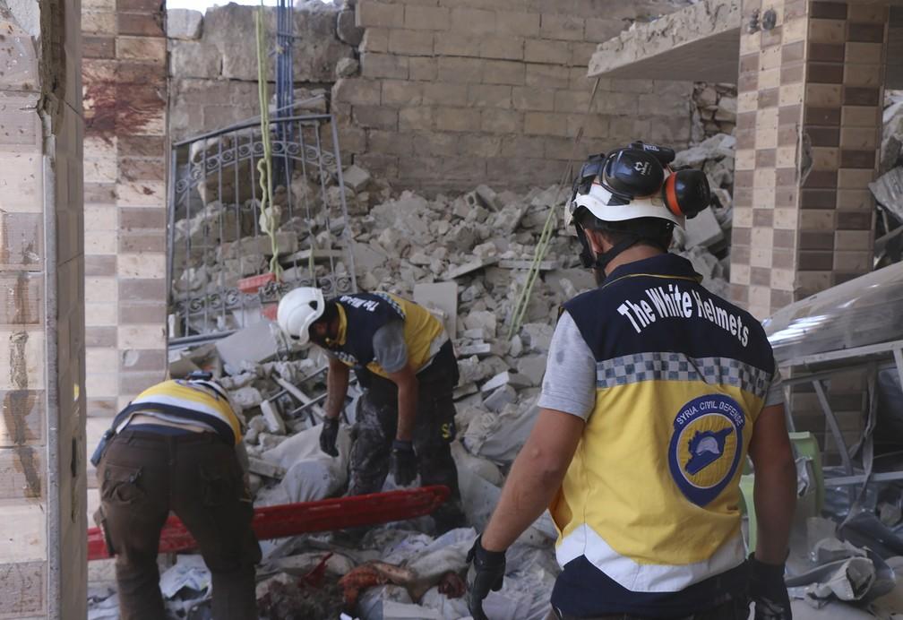 Membros dos Capacetes Brancos da Síria procuram vítimas em prédio destruído por ataques nesta segunda-feira (22), supostamente realizados pelo governo sírio ou pela Rússia. — Foto: Syrian Civil Defense White Helmets via AP