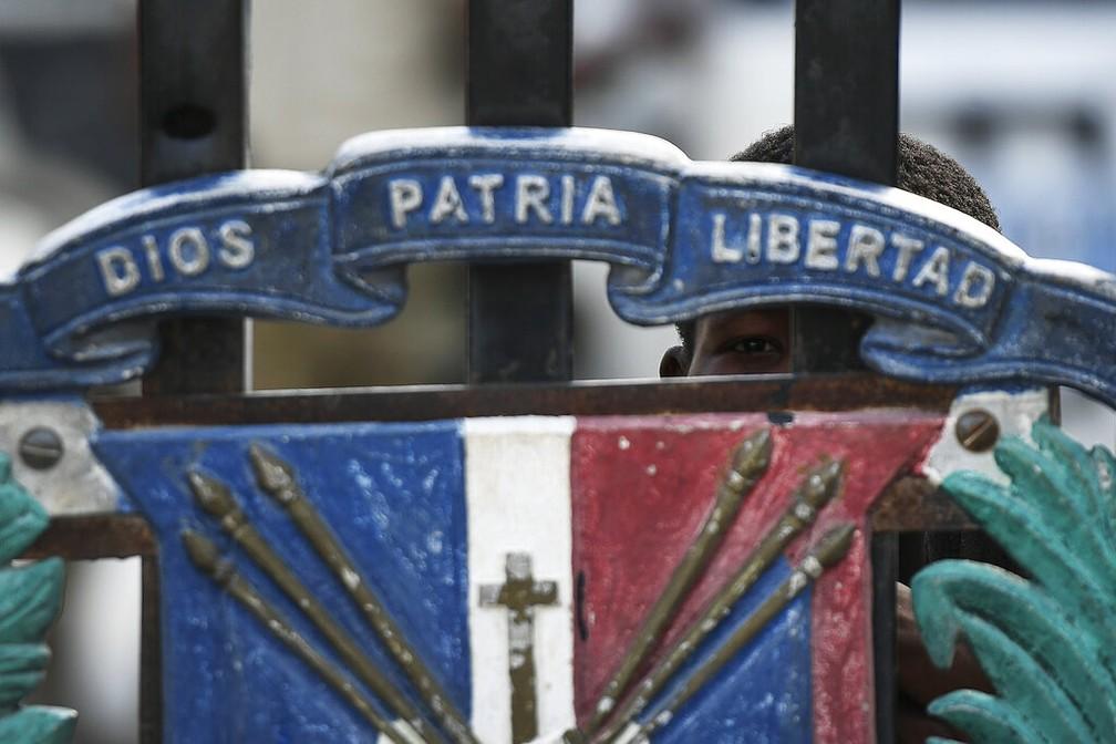 Garoto olha em portão fechado na fronteira entre Haiti e República Dominicana nesta quinta-feira (8) após o governo dominicano fechar a fronteira em sequência à morte de Jovenel Moise, presidente haitiano — Foto: Matias Delacroix/AP Photo