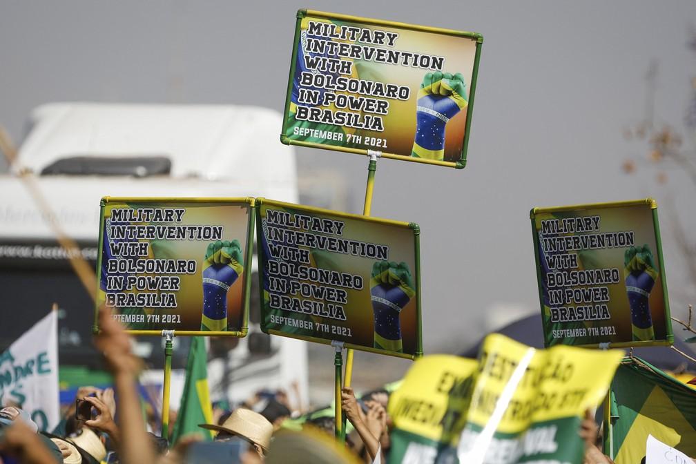 Cartazes, em inglês, pedindo intervenção militar com Bolsonaro no poder, são vistos em atos pró-Bolsonaro em Brasília — Foto: Sergio Lima/AFP
