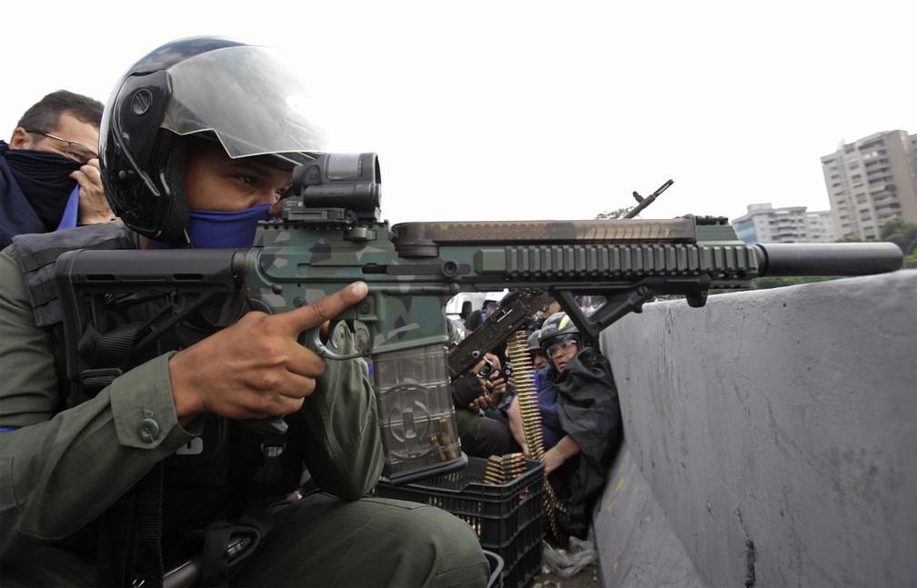 Soldado fiel a Juan Guaidó aponta seu fuzil contra forças de Maduro diante da base aérea 'La Carlota' durante confronto em Caracas — Foto: Boris Vergara/AP