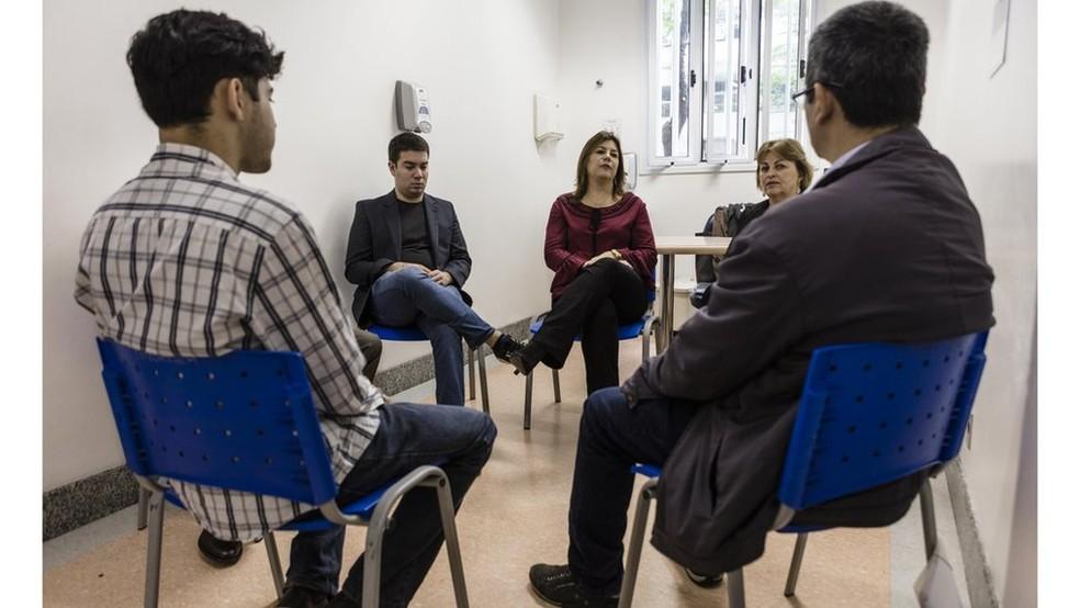 Parte da equipe responsável por atendimentos (de frente, na imagem) e pacientes do grupo de terapia do Hospital das Clinicas da USP (Foto: Gui Christ/BBC Brasil)
