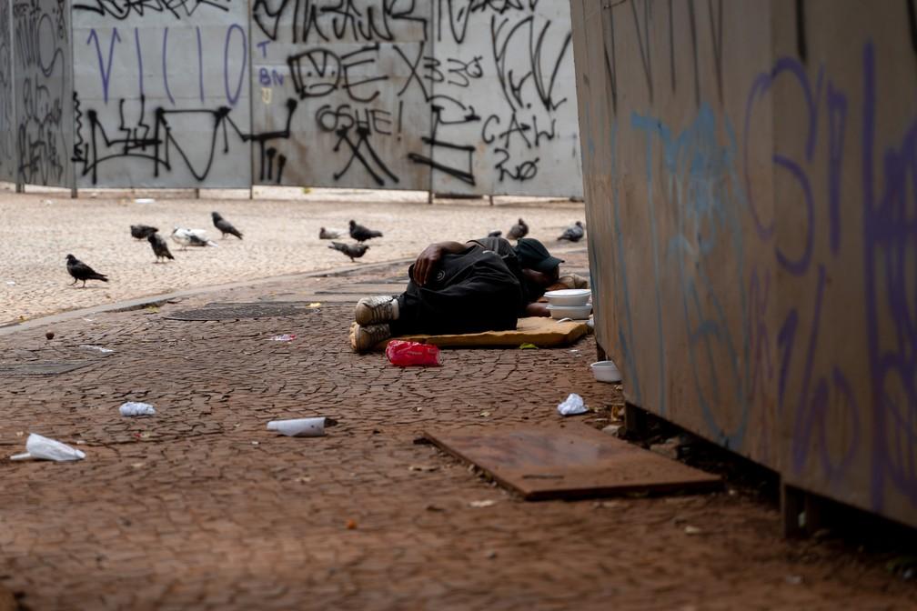 Morador em situação de rua dorme ao lado de tapume no Lardo do Paissandu, Centro de São Paulo, na tarde do dia 8 de janeiro — Foto: Marcelo Brandt/G1