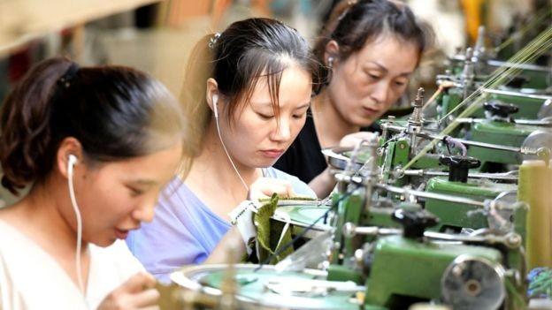 Funcionárias em fábrica chinesa; contra crise global, governo lançou pacote de estímulo (Foto: AFP/BBC)