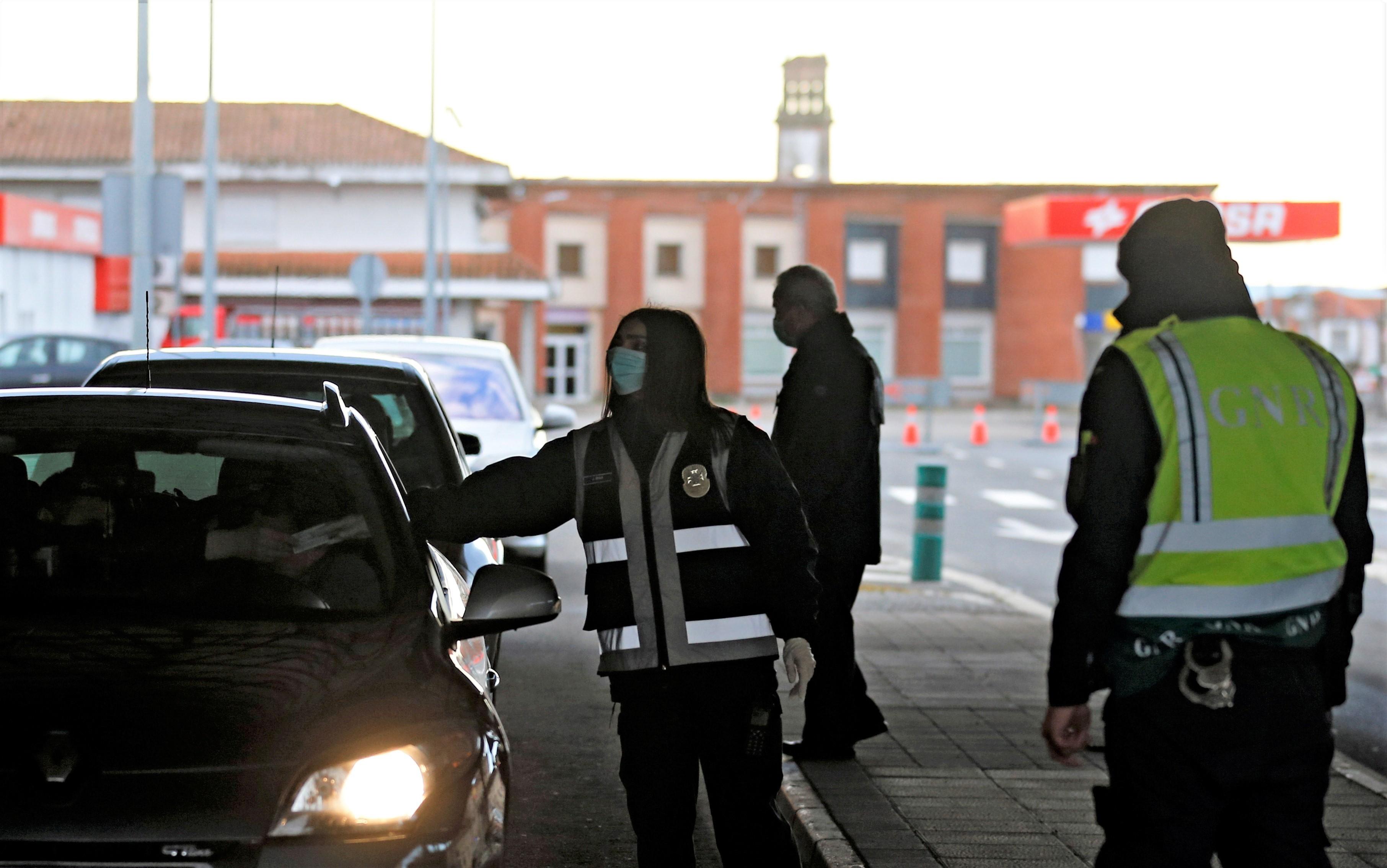 Policiais portugueses checam passageiros de carros na fronteira com a Espanha