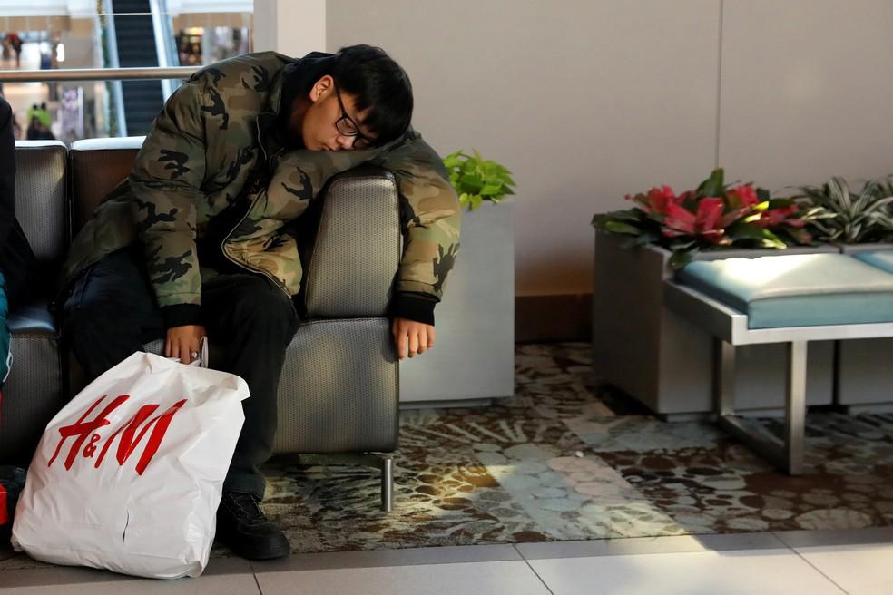 Consumidor dorme durante compras da Black Friday no Roosevelt Field Mall, em Garden City, Nova York — Foto: Shannon Stapleton/Reuters