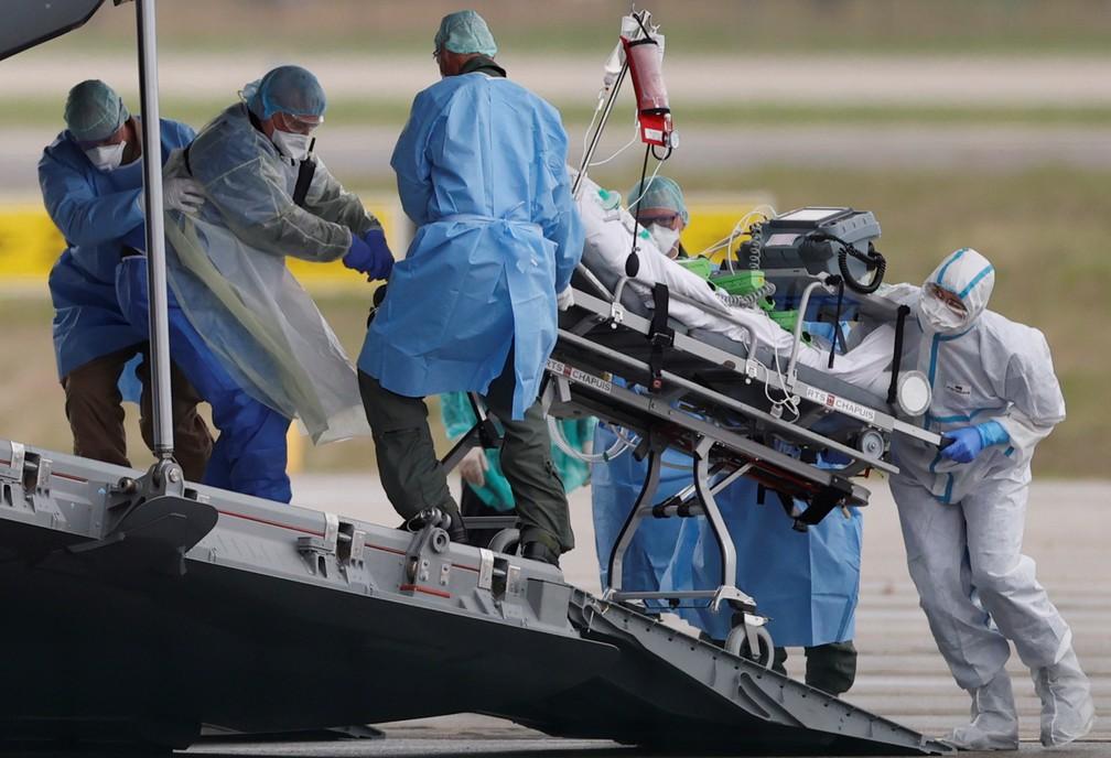 Paciente infectado com Covid-19 é colocado em avião militar alemão para ser transferido de Strasbourg, na França, para Ulm, na Alemanha, neste domingo (29). — Foto: Christian Hartmann/Reuters