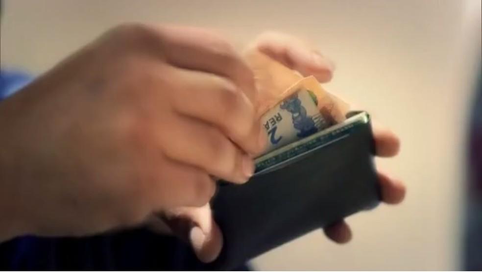 Homem pega dinheiro em carteira — Foto: TV Globo/ Reprodução