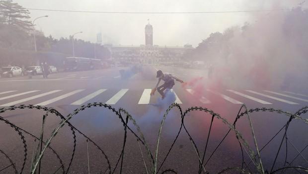Policial coleta granada de fumaça em frente ao palácio presidencial em Taipei, Taiwan, durante as marchas de Primeiro de Maio (Foto: Patrick Lin/Reuters)