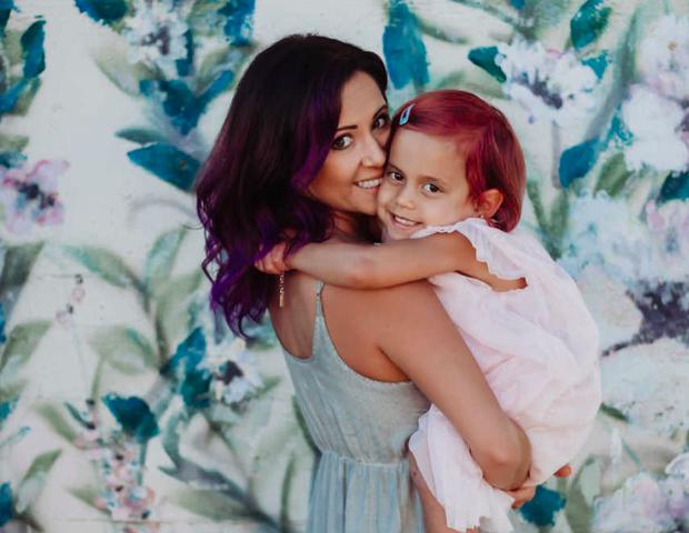A mãe, Janelle, com a filha no colo, já com os cabelos pintados (Foto: Reprodução)