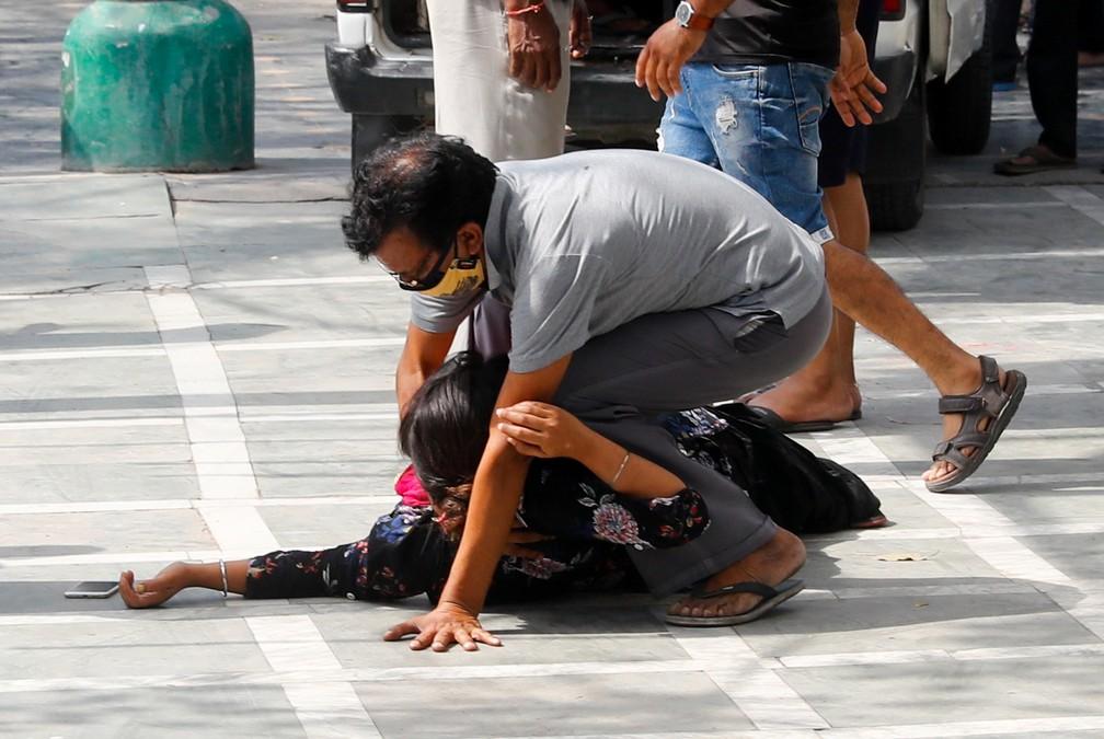 Homem tenta levantar uma mulher que desmaiou após ver o corpo de um parente que morreu de Covid-19 em um crematório em Nova Délhi, capital da Índia, em 30 de abril de 2021 — Foto: Adnan Abidi/Reuters