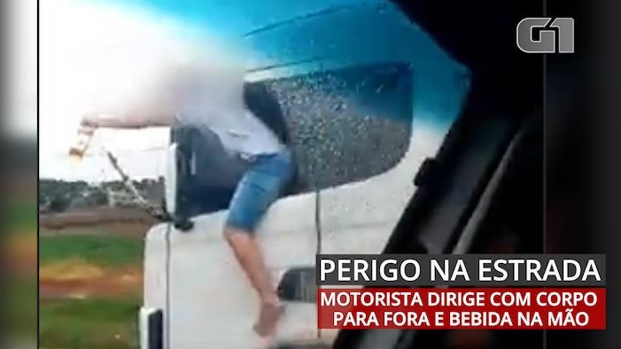 Caminhoneiro é filmado com corpo para fora de veículo com garrafa de bebida na mão