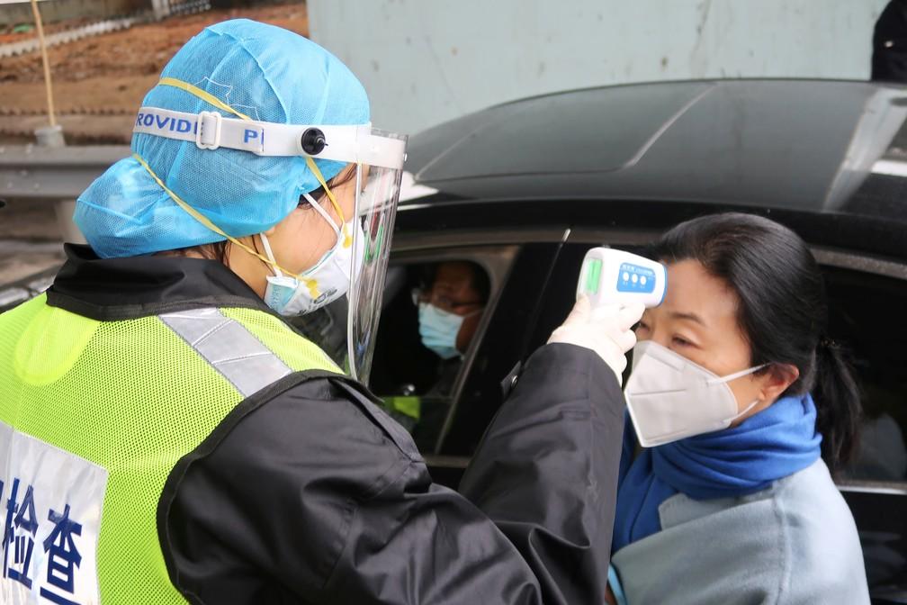 Coronavírus: oficial com máscara protetora verifica temperatura de passageiro em um pedágio entre Xianning e Wuhan, na China, em meio às restrições de circulação de pessoas, que tenta frear a expansão da doença — Foto: Martin Pollard/Reuters.