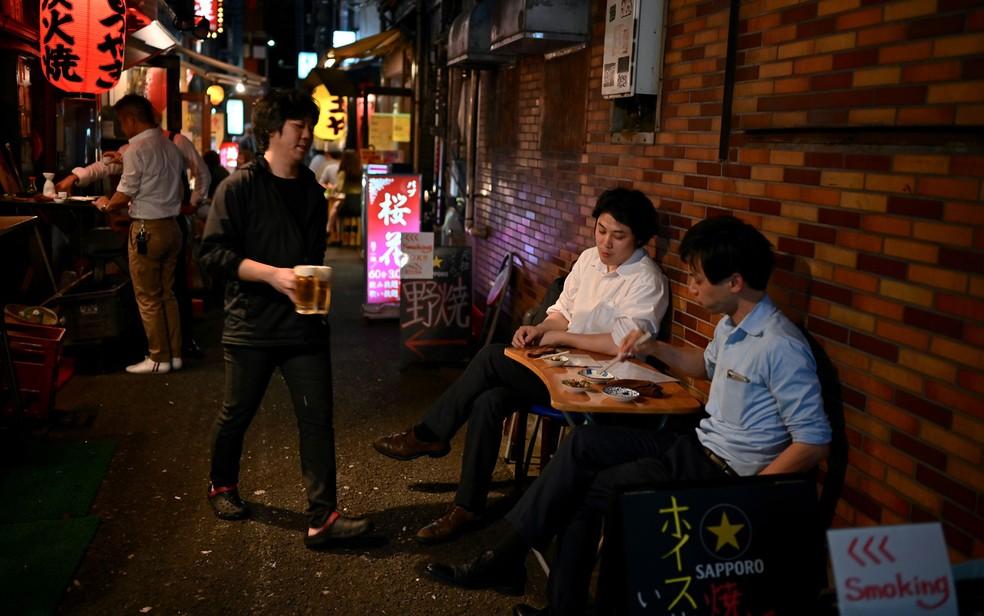 Pessoas bebem em um 'izakaya', bar em estilo informal, no distrito Shinbashi, em Tóquio, no Japão, em 10 de junho — Foto: Charly Triballeau / AFP Photo