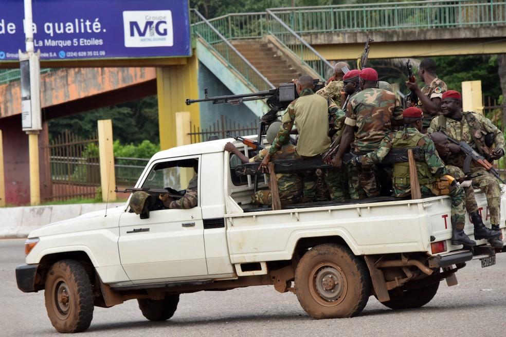 Militares de Guiné em caçamba de caminhonete passam pelo centro de Conakry depois do disparo de tiros no palácio presidencial  — Foto: CELLOU BINANI / AFP