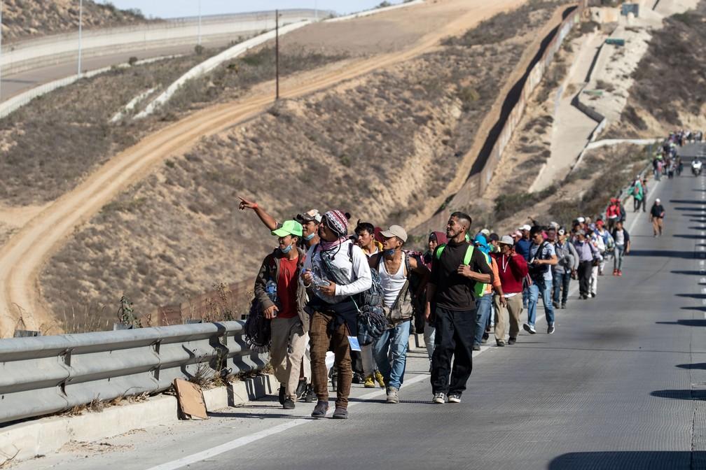 Migrantes caminham perto da fronteira com os EUA, na cidade Playas de Tijuana, no México, na terça-feira (13) — Foto: Guillermo Arias / AFP