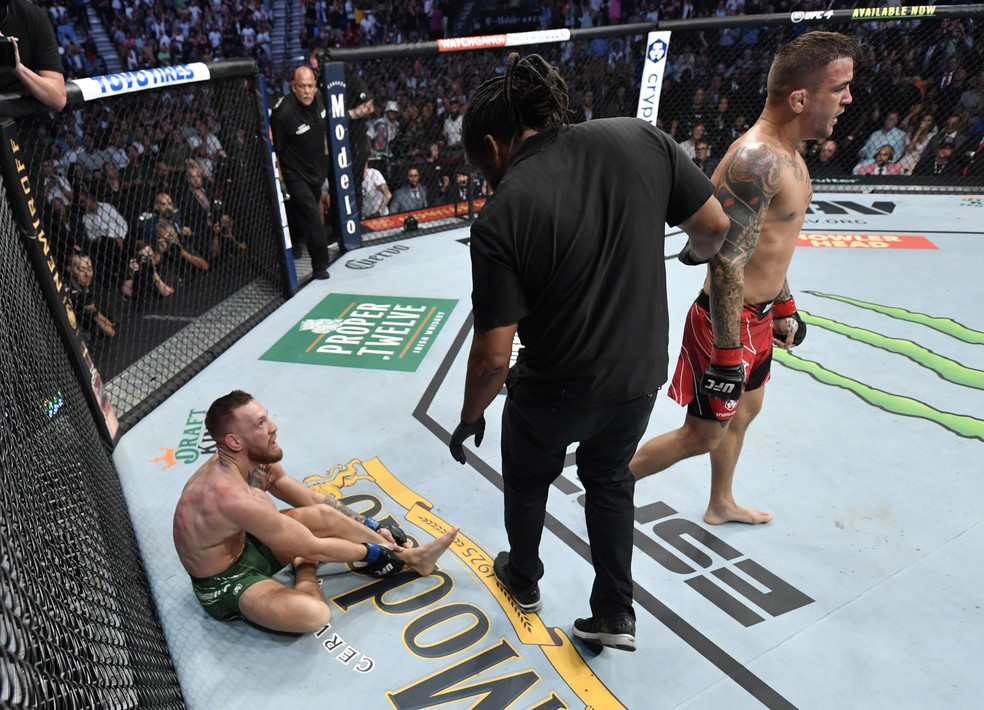 Conor McGregor mostra o tornozelo fraturado ao árbitro Herb Dean na luta contra Dustin Poirier no UFC 264 — Foto: Getty Images