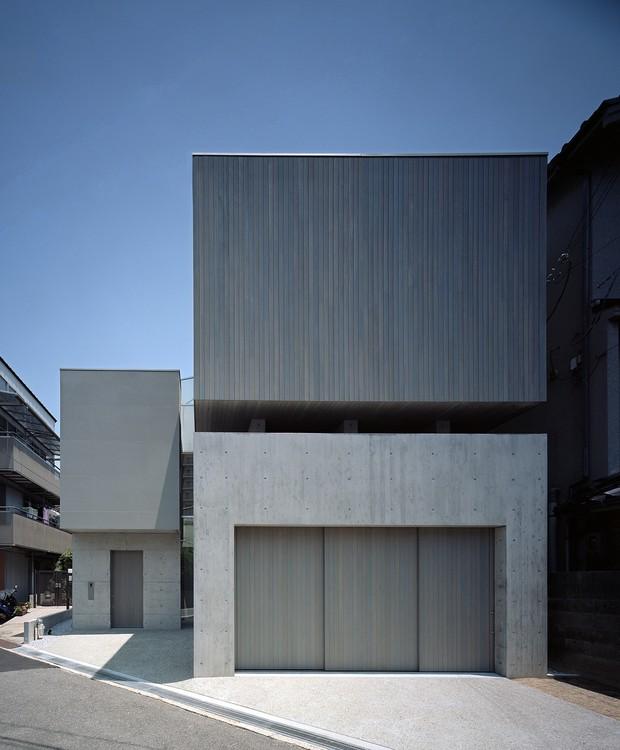 Na fachada de concreto e ripas de madeira, os blocos da casa ficam empilhados com um vão no meio, onde estão instaladas as janelas (Foto:  Katsuya Taira/Studio Rem/ Deezen / Reprodução)