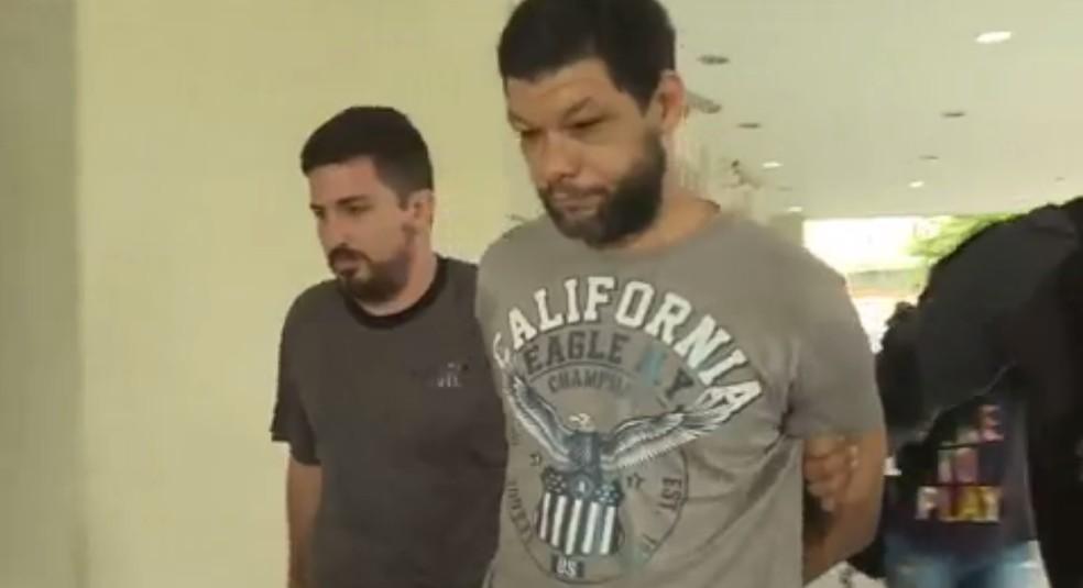 Suspeito chega detido à Cidade da Polícia na Operação Luz da Infância 2 (Foto: Reprodução/GloboNews)