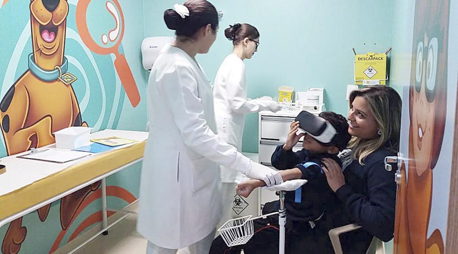 Criança usa os óculos de VR enquanto toma uma injeção (Foto: Estadão Conteúdo)