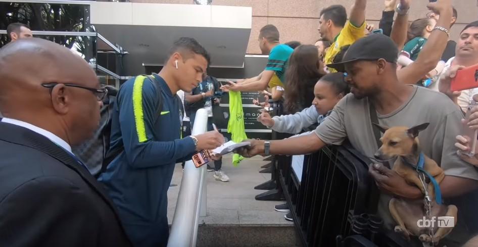 Thiago Silva assinando carteira de trabalho de fã ao embarcar para Arena Corinthians (Foto: Reprodução YouTube)