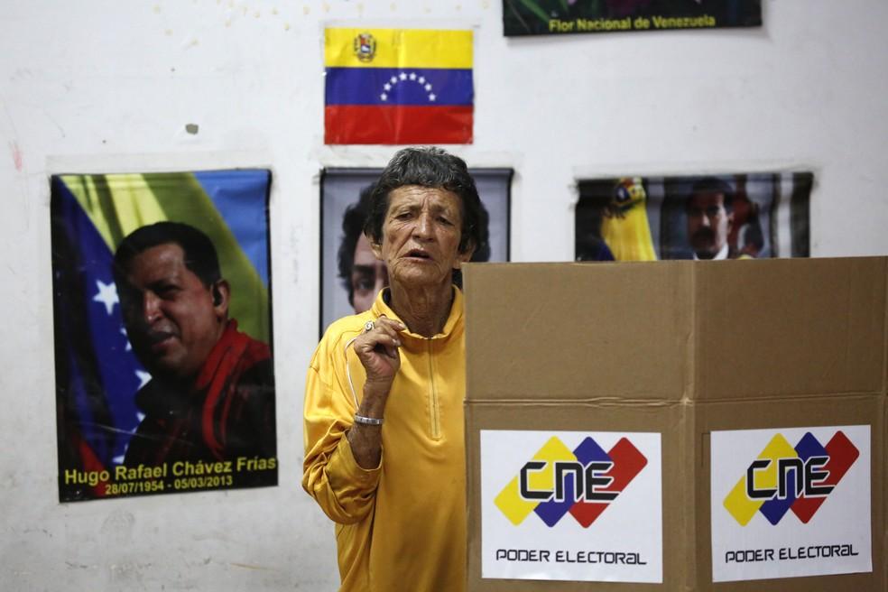 Eleitora deposita seu voto em uma urna em colégio eleitoral de Caracas, Venezuela, neste domingo (30) (Foto: Reuters/Carlos Garcia Rawlins)