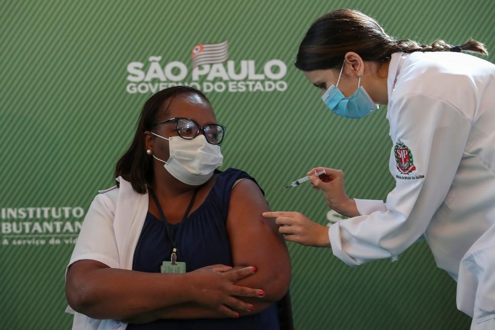 A enfermeira Mônica Calazans, de 54 anos, recebe uma dose da vacina CoronaVac contra a Covid-19 no Hospital das Clínicas, em São Paulo, depois que a Anvisa aprovou seu uso emergencial neste domingo (17). Ela foi a primeira pessoa vacinada no país — Foto: Amanda Perobelli/Reuters