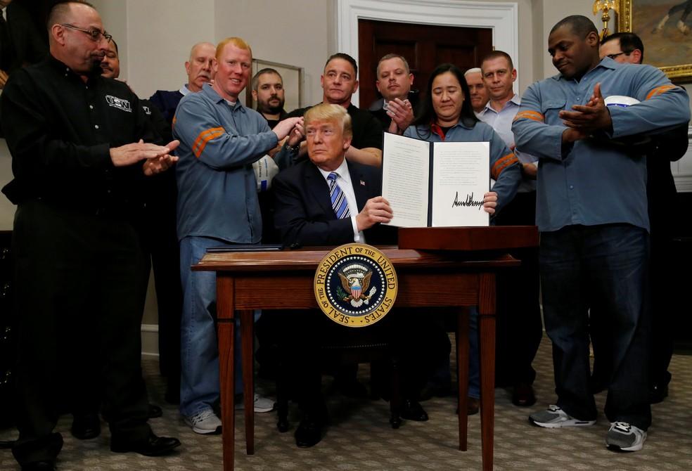 Acompanhado de representantes da indústria do aço e alumínio, Donald Trump assina medida que aumenta tarifas de importação para aço e alumínio (Foto: Leah Millis/Reuters)