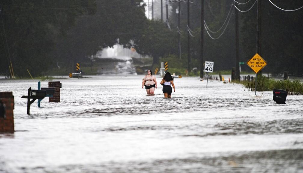 Moradores de Lafayette, na Louisiana (EUA), atravessam rua alagada após passagem do furacão Laura nesta quinta-feira (27) — Foto: Leslie Westbrook/The Advocate via AP