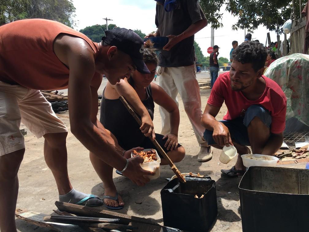 Refugiados cozinham à beira da pista em acampamento nos arredores do abrigo São Vicente (Foto: Emily Costa/G1 RR)